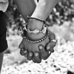 Hands clasped together with intertwined fingers.
